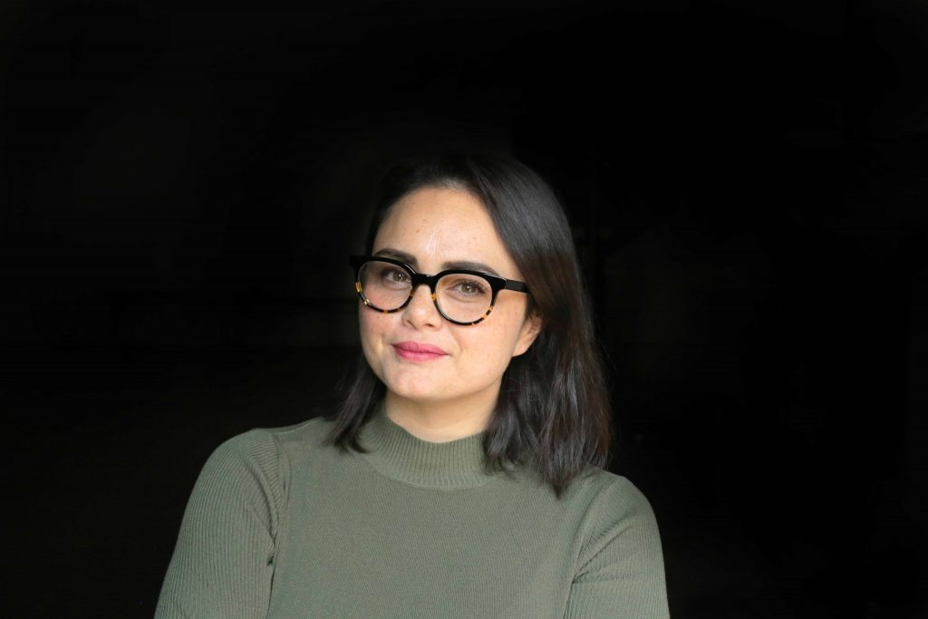 Bronwyn Papantonio looks at the camera against a black background. She wears a khaki green turtleneck and tortoiseshell round glasses and pink lipstick.
