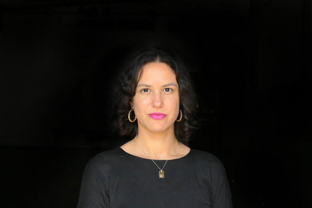 Veronica Barac-Gomez looks at the camera against a black background. She wears a long sleeved black t-shirt, gold necklace and earrings and bright pink lipstick. She has short curly black hair.