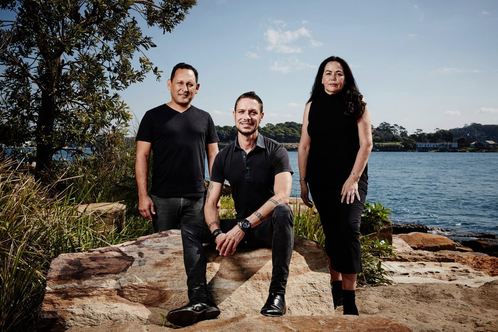 Creative team smile at the camera. They sit on sandstone rocks against a blue water backdrop. They wear black outfits and shoes. To the left of the image are green plant and bush.