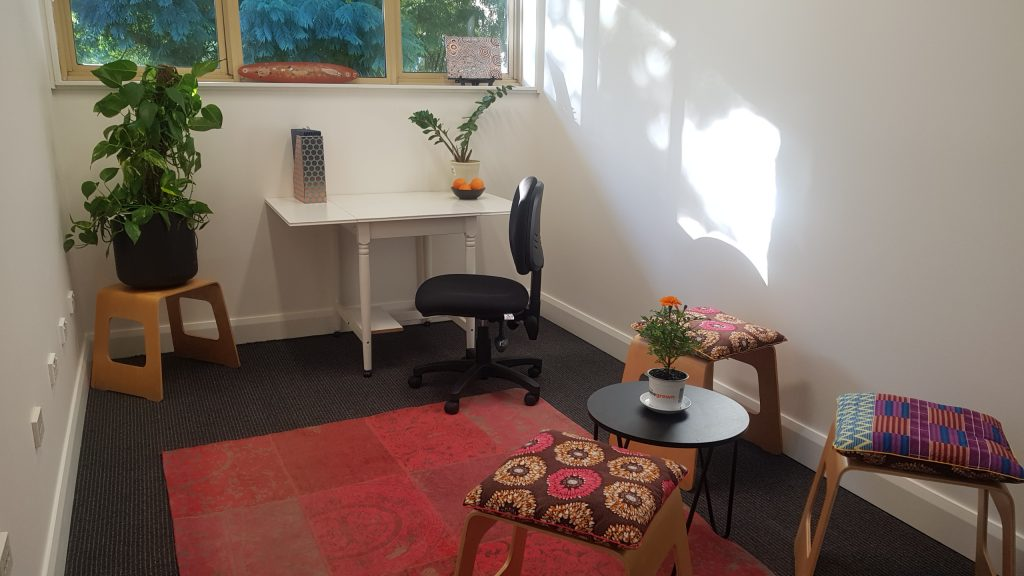 Image of an interior of a studio with white walls, colourful chairs and rug and a small white desk with black chair.